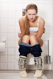 年轻白种人妇女坐洗手间。膀胱 免版税库存图片