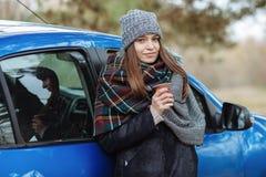年轻白种人妇女室外画象,拿着一个杯子外带的咖啡在森林公园在冷的季节天 穿戴在elega 图库摄影