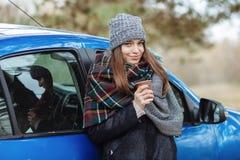 年轻白种人妇女室外画象,拿着一个杯子外带的咖啡在森林公园在冷的季节天 穿戴在elega 库存照片