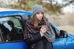 年轻白种人妇女室外画象,拿着一个杯子外带的咖啡在森林公园在冷的季节天 穿戴在elega 免版税库存照片