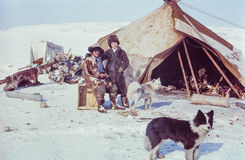 白种人妇女摆在与Chukchi人,当参观土著人民的遥控站时 免版税库存图片