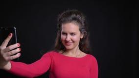 白种人妇女画象微笑地做selfie照片的红色的使用智能手机在黑背景 影视素材