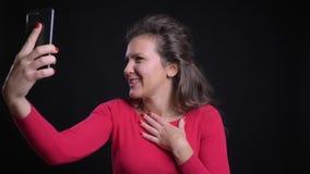 白种人妇女画象红色的微笑地谈话在videochat使用在黑背景的智能手机 股票视频