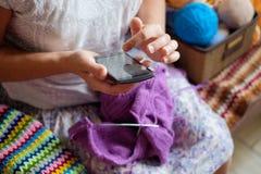 白种人妇女编织羊毛衣裳 拿着在手的编织针 免版税库存照片