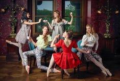 白种人姿势饮用的茶的时尚快乐的芭蕾舞女演员 图库摄影
