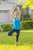 白种人实践的女子瑜伽 库存图片