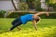 白种人实践的女子瑜伽 免版税图库摄影