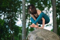 白种人实践的瑜伽,站立的手中平衡锻炼, Bakasana姿势侧视图  库存图片