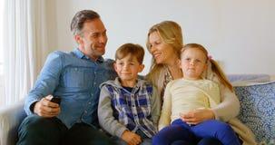 白种人家庭正面图坐长沙发和观看的电视在一个舒适的家4k 股票录像