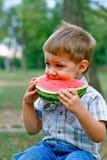 白种人小男孩吃片式西瓜 库存照片