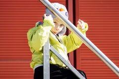 白种人小男孩画象有滑稽的表情的 孩子保持楼梯栏杆和戏剧在街道围场 免版税图库摄影