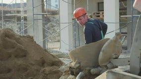 白种人工作者倾吐沙子入一台混凝土搅拌机由铁锹在建造场所 影视素材