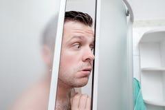 白种人年轻人身分在充满恐惧的卫生间里在他的眼睛 免版税图库摄影