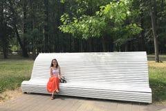 白种人年轻深色的妇女坐一条白色长凳在公园并且调查照相机在一个晴朗的夏日 免版税图库摄影