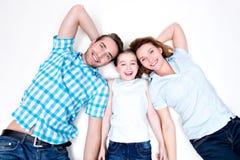 白种人愉快的微笑的年轻家庭大角度画象  免版税库存照片