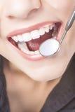 白种人有牙医口镜的妇女白色牙 免版税库存图片