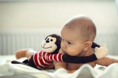 白种人有被充塞的猴子拥抱玩具肚子时间wimdow光的女孩男孩婴儿新出生的婴孩 库存图片