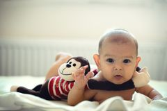 白种人有被充塞的猴子拥抱玩具肚子时间wimdow光的女孩男孩婴儿新出生的婴孩 图库摄影