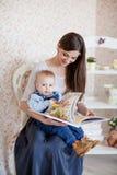 白种人母亲和她的孩子读了一本书 库存照片