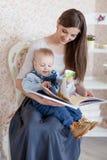 白种人母亲和她的孩子读了一本书 免版税库存照片