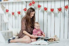 白种人母亲和她的孩子读了一本书 库存图片