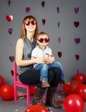 年轻白种人母亲坐与男婴小孩的小桃红色椅子她的膝部膝盖在戴滑稽的眼镜的演播室 库存图片
