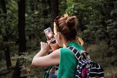 年轻白种人深色的妇女在森林里拍照片 免版税库存图片