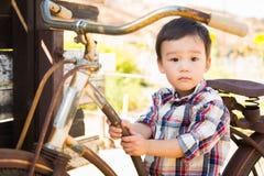 白种人混合的族种和获得中国年轻的男孩在Bic的乐趣 免版税库存照片