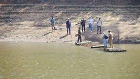 白种人游人在木筏停泊对湖银行在公园 股票录像