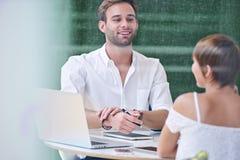 白种人男人和妇女之间的互作用在早晨业务会议期间 免版税库存图片