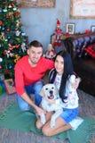 白种人男人和妇女坐与白色狗近的装饰的圣诞树的地板 免版税库存照片