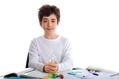白种人男孩拿着一个电灯泡,当做家庭作业时 库存图片