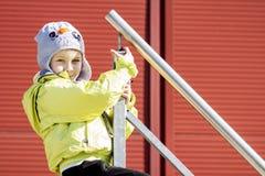 白种人男孩画象帽子和夹克的在楼梯栏杆  男孩保持栏杆并且微笑 免版税库存图片
