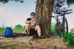 白种人男性休息在树下的骑自行车者活跃生活方式在行使从瓶的自行车饮用水以后 运动员 库存图片