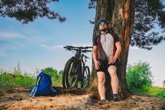白种人男性休息在树下的骑自行车者活跃生活方式在行使从瓶的自行车饮用水以后 运动员 库存照片