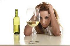 白种人白肤金发的被浪费的和沮丧的醺酒的妇女饮用的白葡萄酒玻璃被喝的宿酒 免版税库存图片