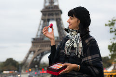 年轻白种人的妇女拿着法国蛋白杏仁饼干 免版税库存图片