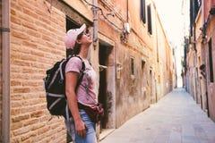 白种人的旅游女孩在一条老离开的街道上站立在威尼斯在意大利并且在夏天查寻 库存照片