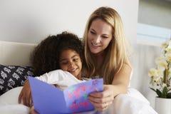 白种人看生日贺卡的妈咪和黑人女儿 免版税图库摄影