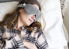 白种人睡觉在床上的妇女佩带的眼罩 库存图片