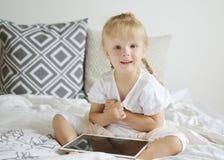 白种人矮小的白肤金发的女孩在床,家内部,现代设备技术上的打片剂比赛 免版税库存照片