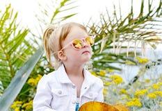 白种人矮小的白肤金发的女孩走的热带庭院 免版税库存照片