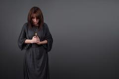 白种人纵向祈祷的妇女年轻人 祷告女孩在一位尼姑的外衣穿戴了灰色演播室背景的 免版税库存图片