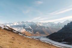 白种人结算天数highmountains山10月俄国星期日 晃动在上部Balkaria的Likoran在云彩 秃头山冬天风景  免版税库存图片