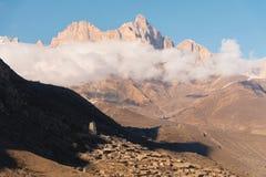 白种人结算天数highmountains山10月俄国星期日 晃动在上部Balkaria的Likoran在云彩 秃头山冬天风景  图库摄影