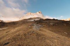 白种人结算天数highmountains山10月俄国星期日 晃动在上部Balkaria的Likoran在云彩 秃头山冬天风景  库存照片