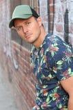 白种人美国人偶然街道时尚在纽约,佩带的蓝色花仿造了衬衣,绿色盖帽,坚持街道画 图库摄影