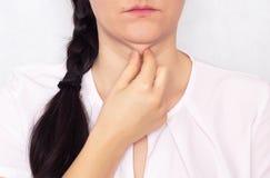 白种人美女拉扯她的手一个双重肥胖下巴,一个垂悬的下巴,白色背景的一个问题 免版税库存照片