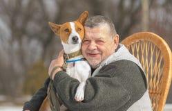 白种人老人室外画象有他逗人喜爱的basenji狗的 免版税库存图片