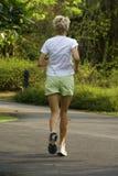 白种人跑步的夫人公园 图库摄影